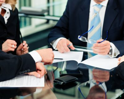 Business - meeting in an office; lawyers or attorneys discussing a document or contract agreement